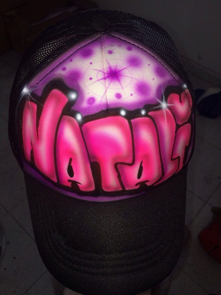 כובע גרפיטי שחור עם שם על רקע סגול